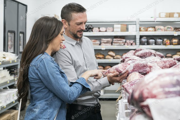 Mid adult woman and man shopping in grocery store, smiling.