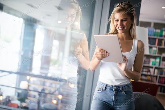 Schöne glückliche Frau halten Tablette beim Lächeln