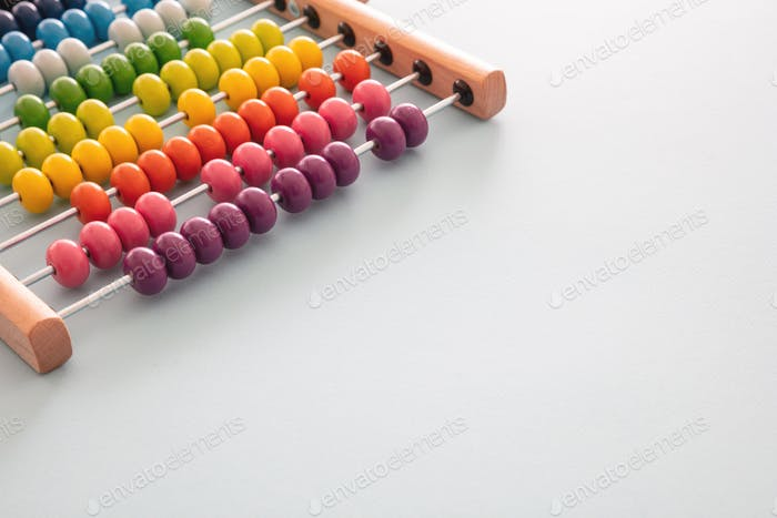 School abacus with colorful beads on blue color background, close up view