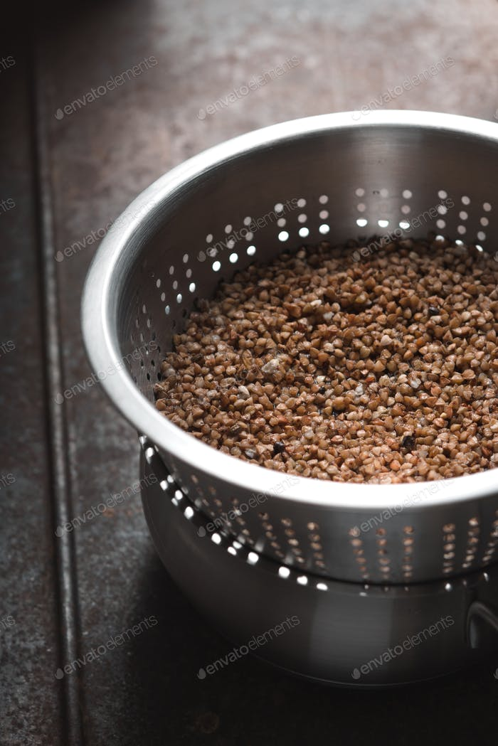 Buckwheat in the metal  colander vertical