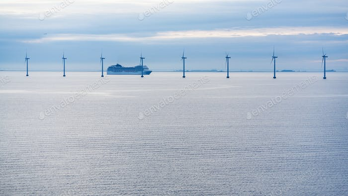 ferry near offshore wind farm in morning twilight