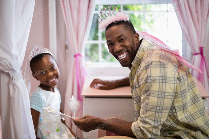 Happy father and daughter wearing costume wings at home
