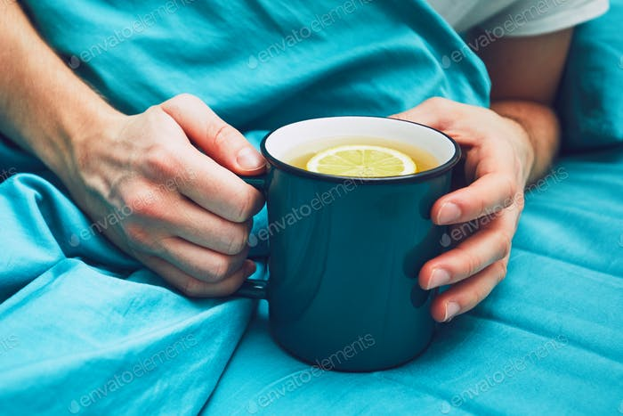 Sick man with hot tea in the bed