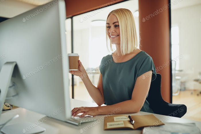 Smiling businesswoman working on a computer and drinking coffee