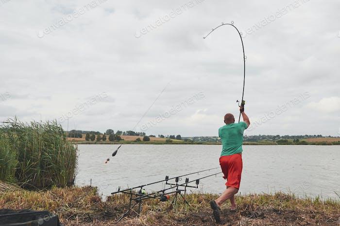 Der Fischer wirft einen Köder mit Köder. Heute wird er einen großen Fisch fangen. Jagd- und Hobbysport