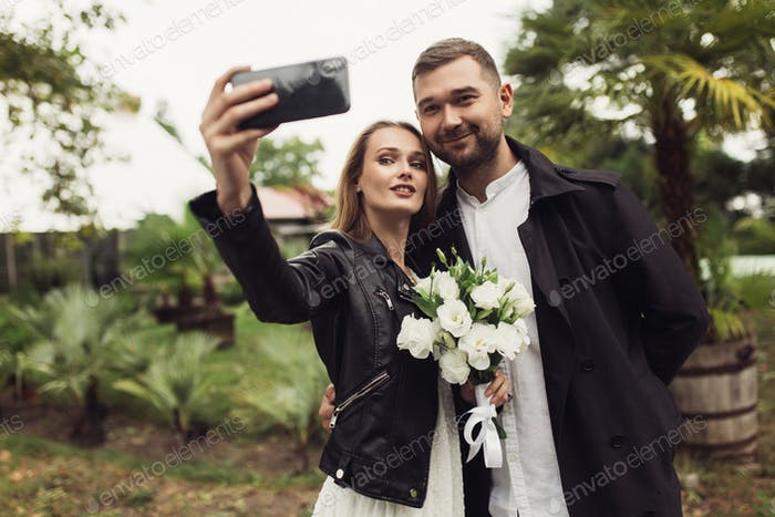 Young joyful man in trench coat and beautiful smiling woman in b