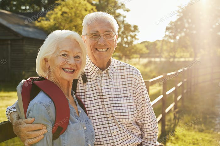 Portrait Of Senior Couple Hiking In Countryside Together