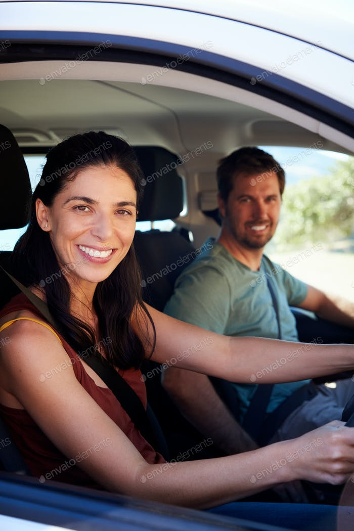Mid adult white woman driving car, husband in front passenger seat smiling to camera, vertical