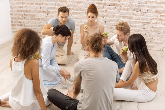 Group of young multi-ethnic beautiful couples sitting together and smiling talking eating