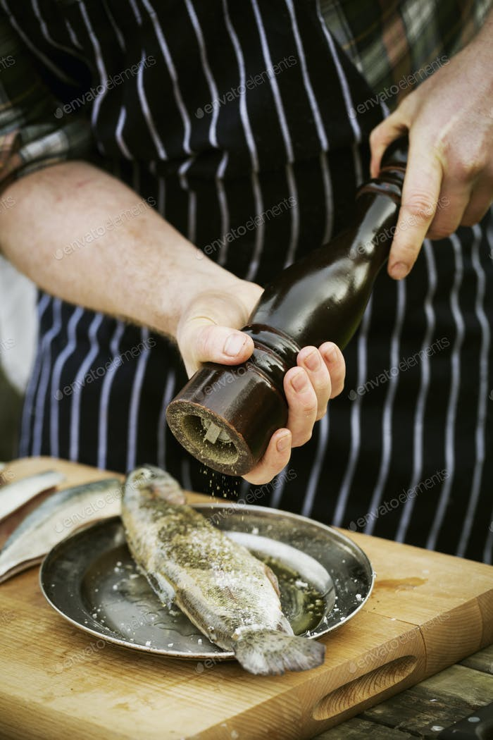 Chef using a salt mill, grinding salt onto a fresh fish.