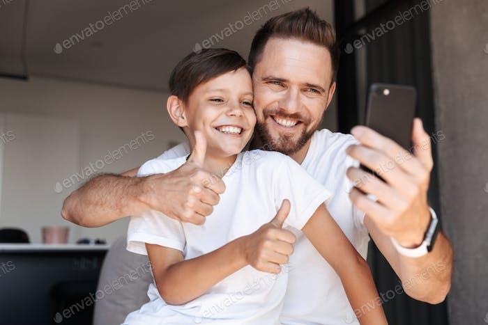 Bärtiger Mann drinnen zu Hause mit seinem Sohn nehmen ein Selfie.