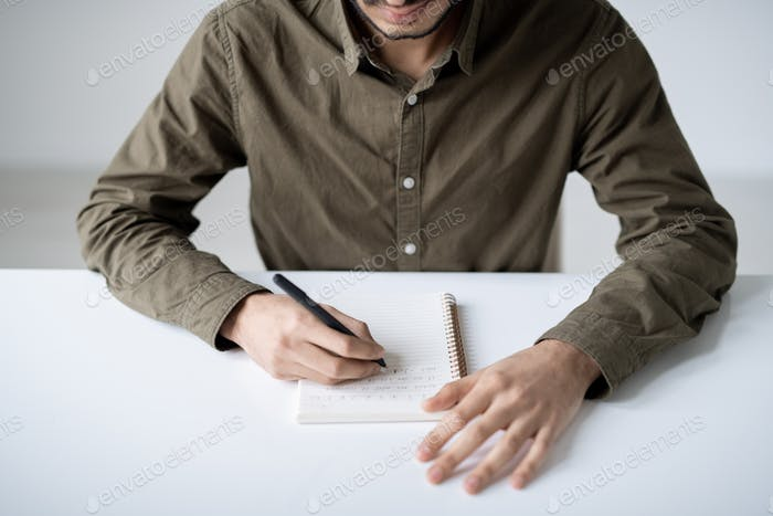 Young student in casualwear making notes on page of copybook by desk