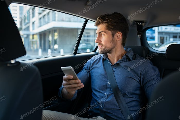Man sitting in car using smart phone