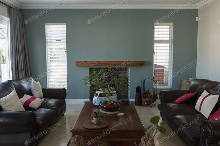 Living room with two sofas separated by a low table and an armchair in front of the fireplace