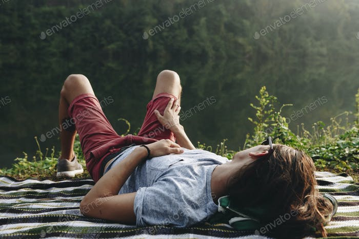 Man relaxing by a lake in the forest