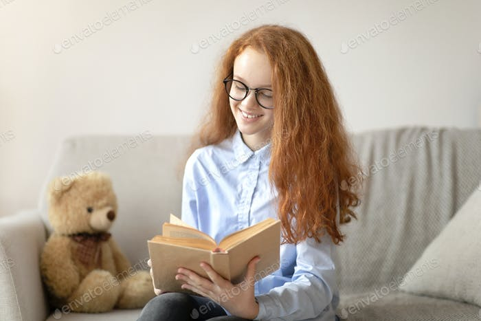 Girl wearing glasses, sitting on the couch, reading book