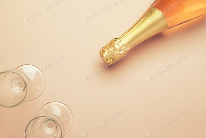Bottle with pink sparkling wine or rose champagne and glasses