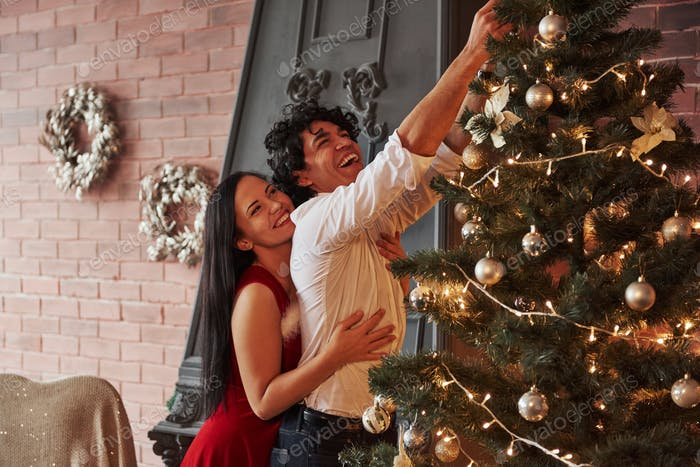Romantic couple dressing up Christmas tree in the room with brown wall and fireplace