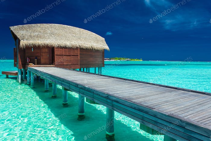 Over water bungalows with steps into coral lagoon, Maldives