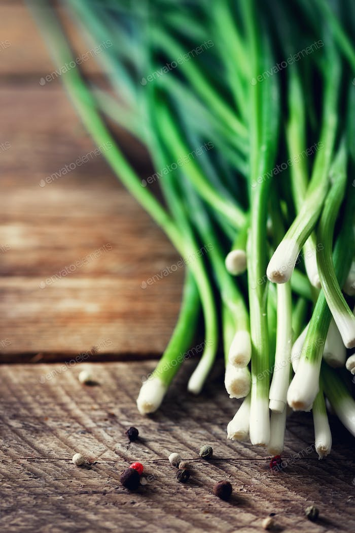 Bunch of fresh organic green onions, scallions on wooden background with pepper. Copyspace