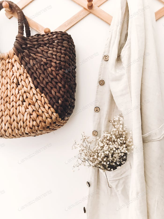 Stylish wooden hanger with straw bag, linen tote bag, brown hat and linen cloth