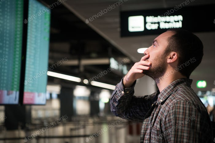 Young man in airport near flight timetable