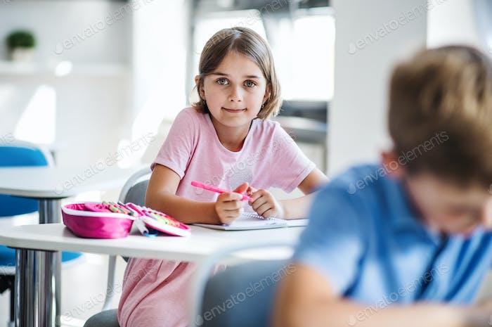 Ein kleines Schulmädchen sitzt am Schreibtisch im Klassenzimmer und schaut auf die Kamera.