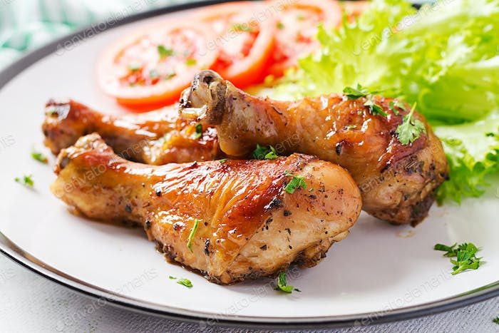 Grilled chicken legs with spices and fresh vegetables. Baked drumsticks.