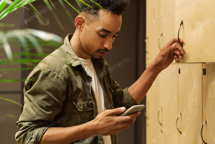 Side view of young attractive casual African American guy dreamily using cellphone in locker room