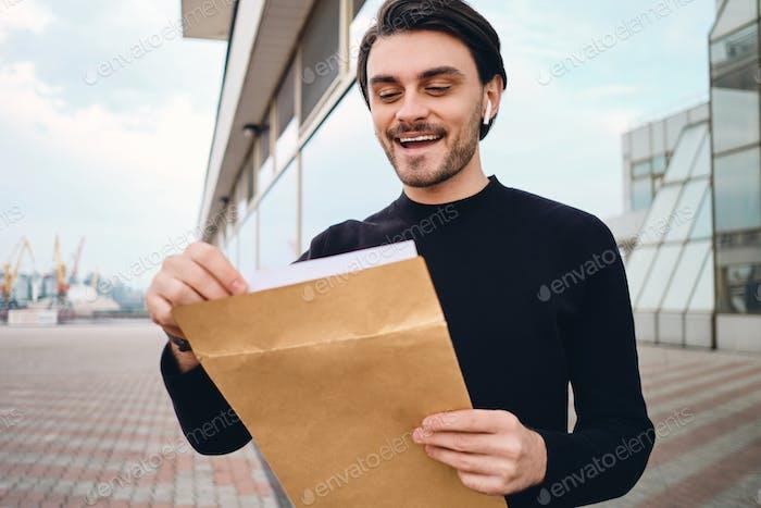 молодой веселый брюнетка человек счастливо открытие конверт с ответ от работа открытый