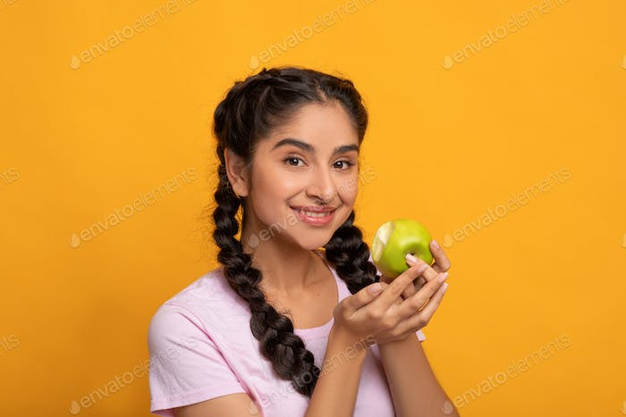 Portrait of a cheerful young woman holding bitten green apple