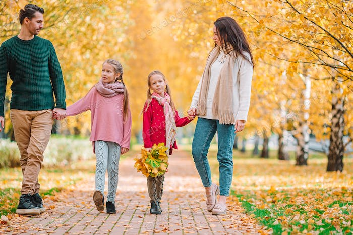 Portrait of happy family of four in autumn day