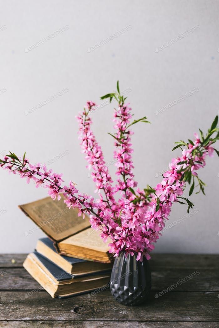 Bouquet of flowers and old books on an old wooden board with copy space. Vintage decor.
