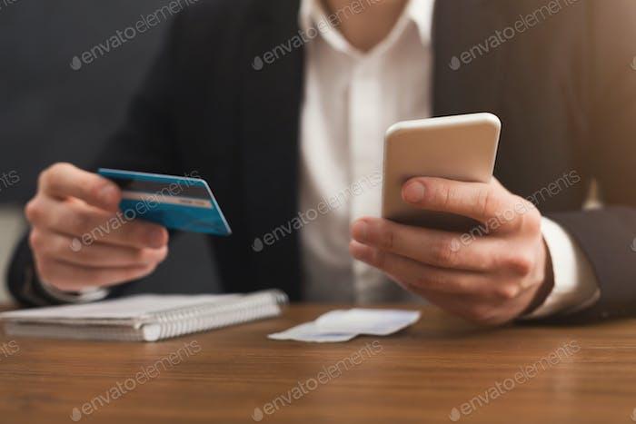 Die Hände des Mannes halten eine Kreditkarte und mit Smartphone