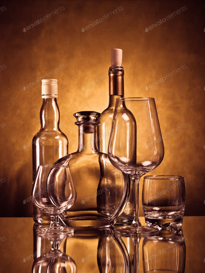 Whiskey, cognac and wine bottles with glasses