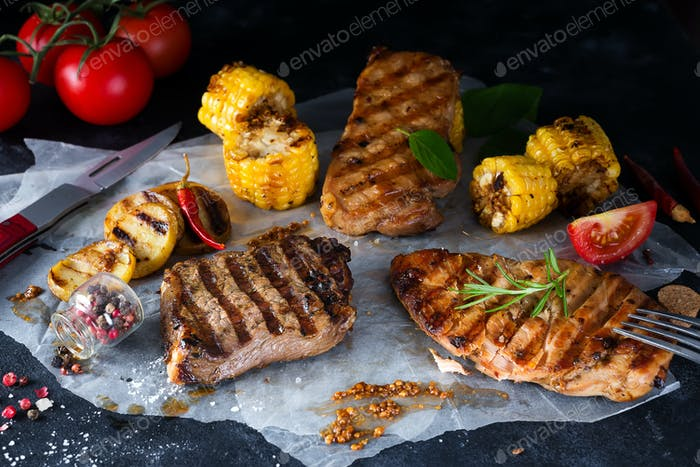 Grilled steak and vegetable , baked potatoes and green salad on dark