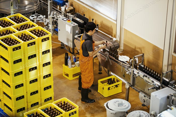 Worker standing next to yellow plastic crates with beer bottles in a brewery.