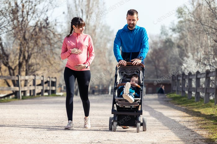 Sporty young couple with her little son walking while enjoying the time together outdoor.