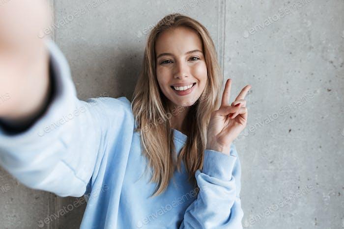 Fröhliche glückliche hübsche Frau, die Friedensgeste zeigt.