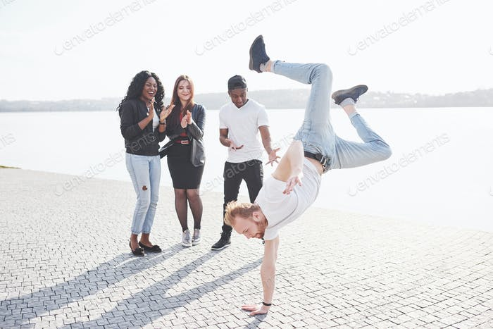 Street artist breakdancing outdoors. Surprised friends applaud