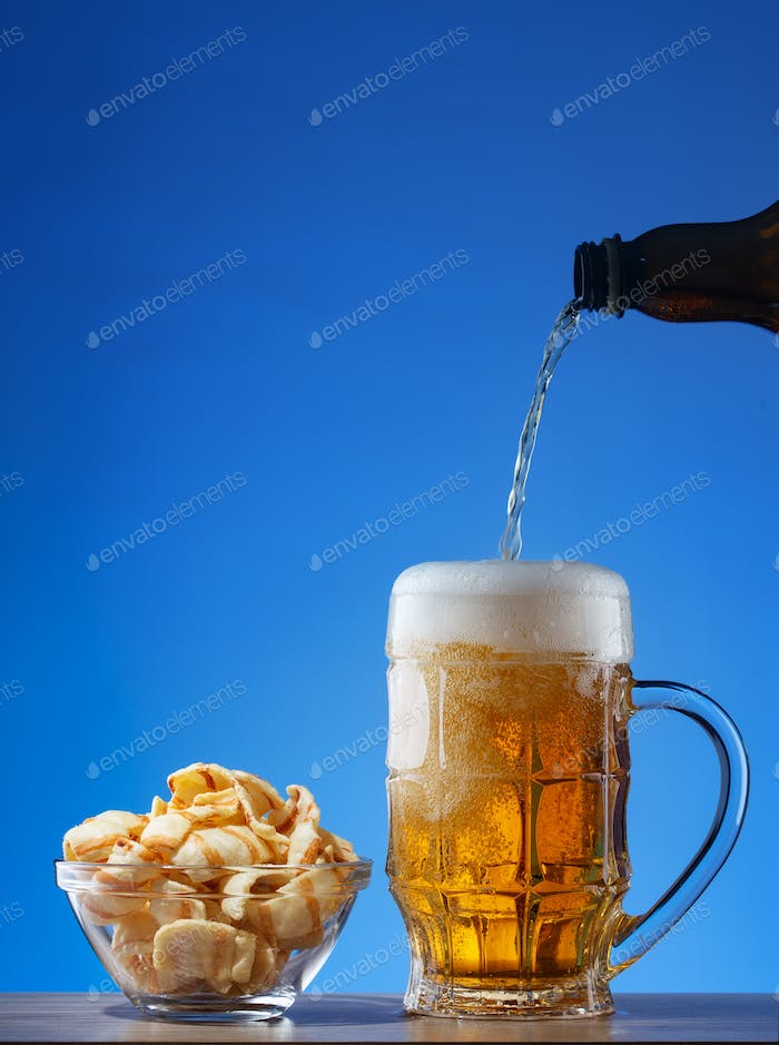 Light beer poured into mug and snacks in plate on blue background