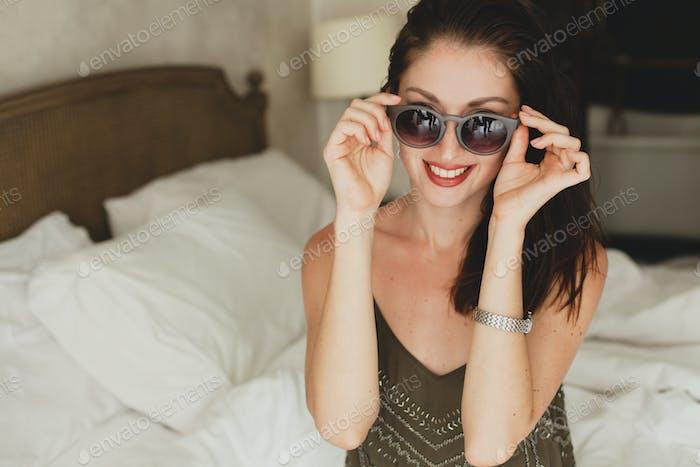 joven hermosa mujer sentada en la cama en la habitación de hotel