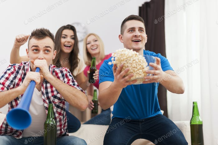 Young group of people celebrating win of favourite sports team