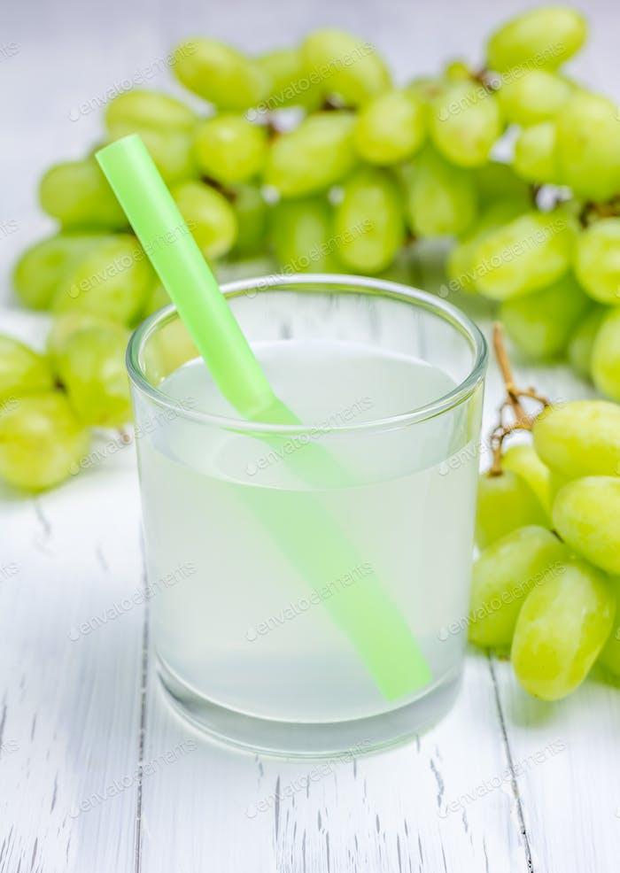 Glas weißen Trauben Saft und Trauben auf dem Hintergrund