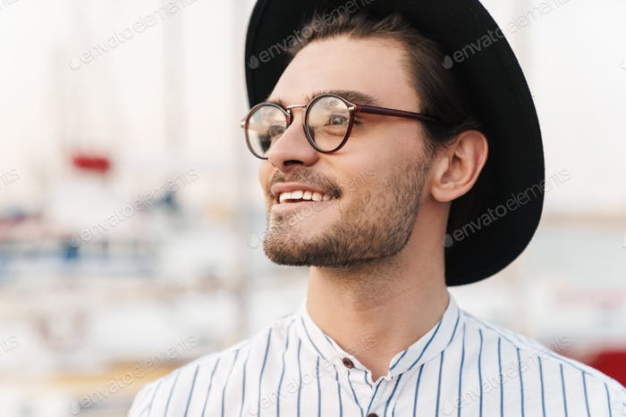 Photo of happy unshaven man looking aside and smiling while walking on pier