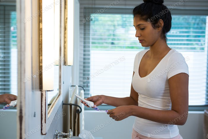 Woman holding toothbrush in bathroom