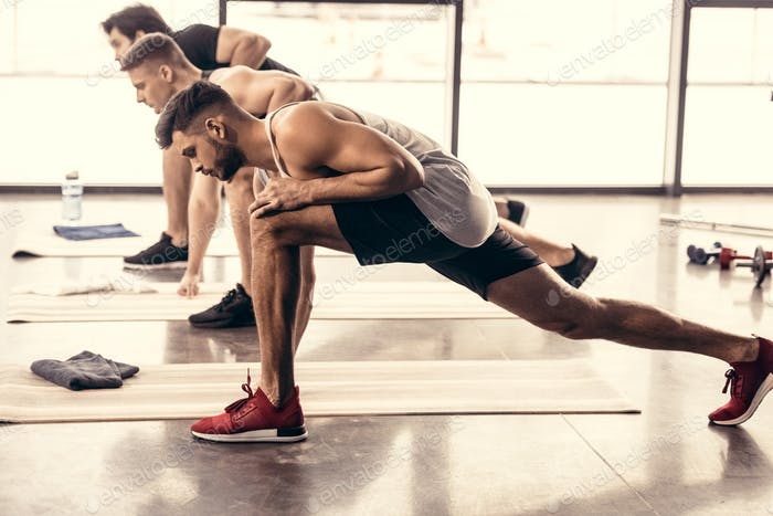 handsome sportsmen simultaneously stretching legs in gym