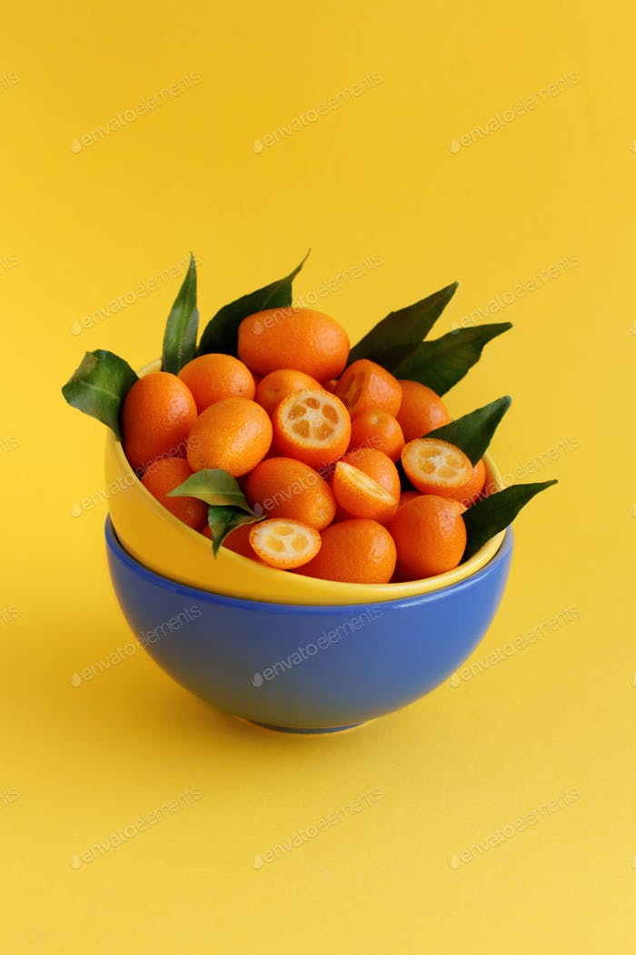 Kumquat fruits on a yellow background