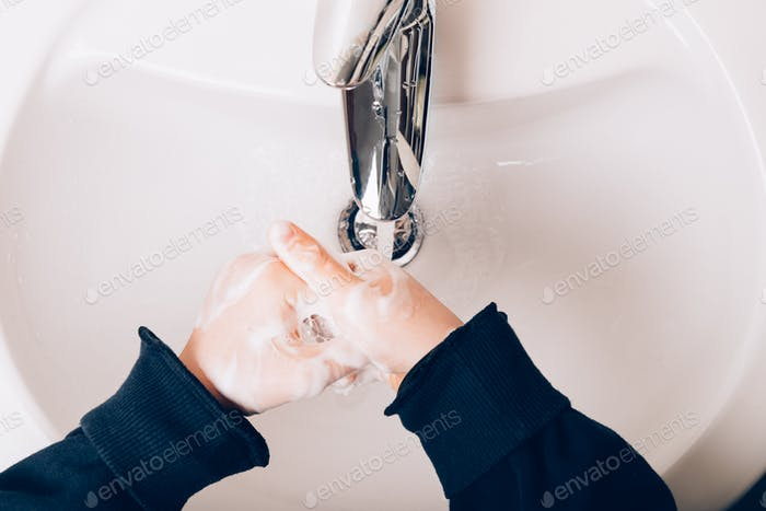 The gils is washing hands with soap