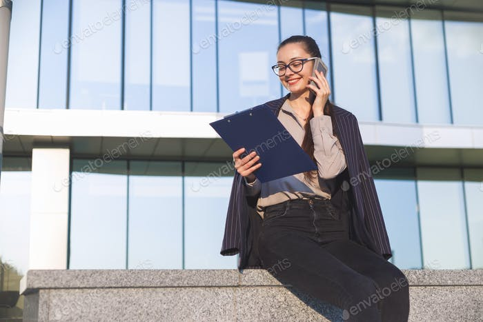Businesswoman with folder speaking on the phone